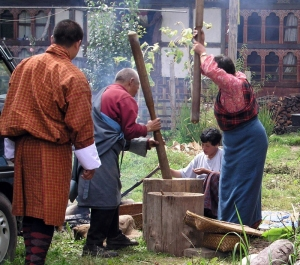 Bhutanese family beating rice